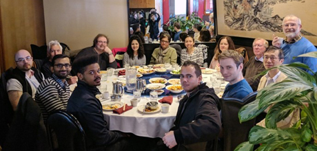 Cameron Gordon's post-lecture lunch with faculty and students all gathered around a table with food.