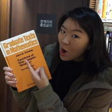 A photo of a student in Korea pointing to John Conway's book: Graduate Texts in Mathematics.
