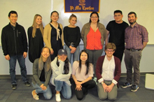 2018 inductees of Pi Mu Epsilon honor society standing with Professor Mintchev in front of a purple and gold Pi Mu Epsilon banner.