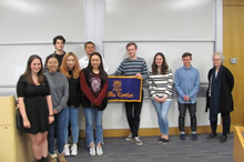 2019 inductees of Pi Mu Epsilon honor society standing with Professor Gorkin while holding a purple and gold Pi Mu Epsilon banner.