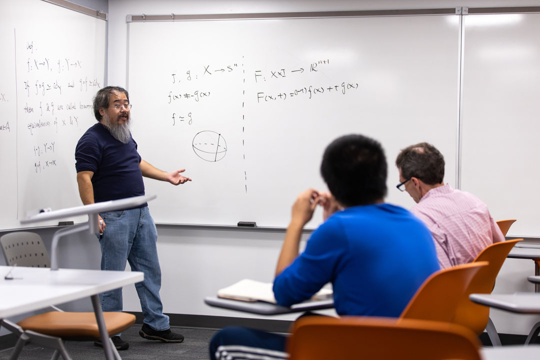 Professor speaking in front of equations on a whiteboard with two students in the foreground