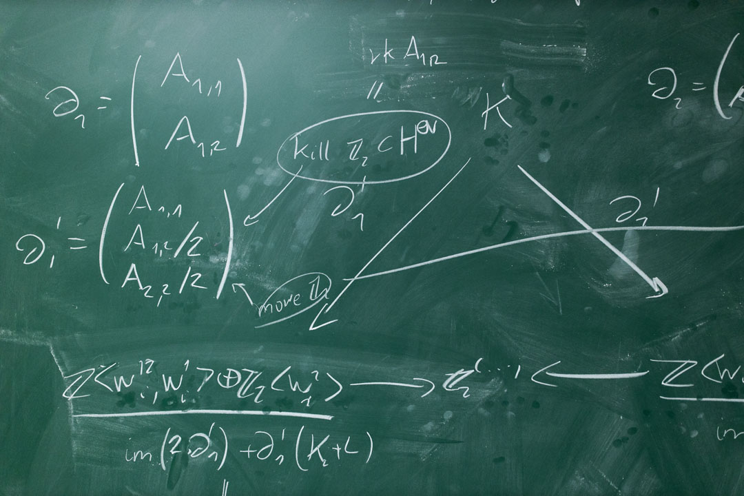 A green chalkboard covered in mathematical equations