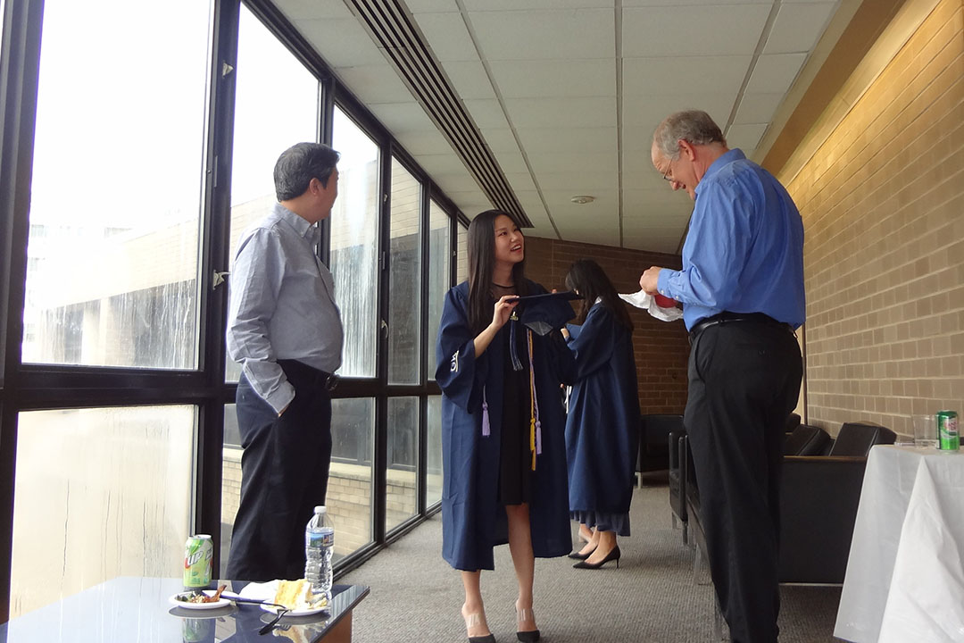 A mathematics graduate wearing a cap and gown talks to two professors at an event