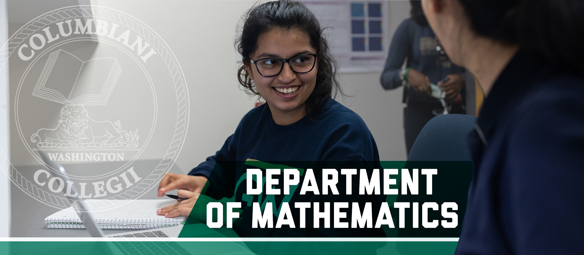Two students working in a classroom. Department of Mathematics, Columbian College seal